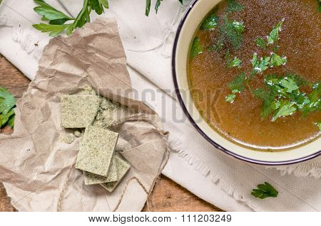 Bouillon Cubes Next To A Bowl Of Broth