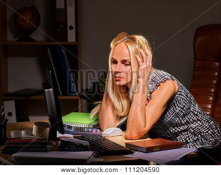 Woman at computer late at night take head. Social network addiction.