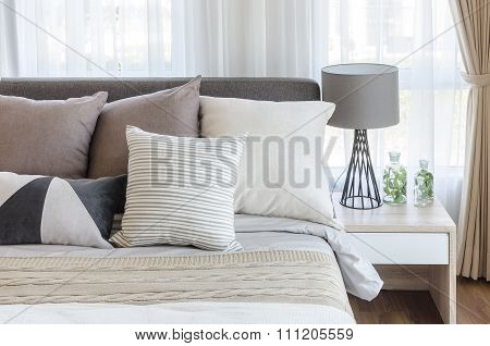 Modern Style Bedroom With Pillows On Bed And Modern Grey Lamp On Side Table