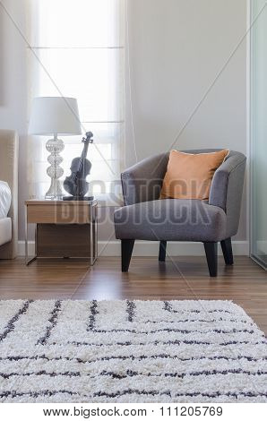 Orange Pillow On Modern Grey Chair With Bedside Table And White Lamp In Bedroom