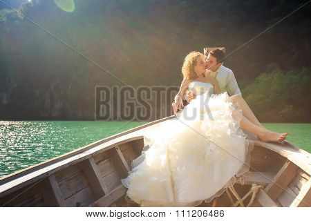Groom Kisses Blonde Bride In Fluffy On Nose Of Longtail Boat