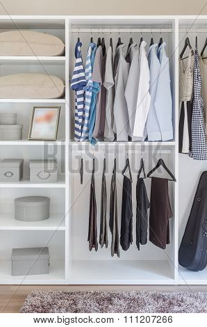Clothes Hanging In White Wardrobe