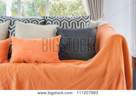 Living Room With Orange Color Blanket With Pillows On Sofa