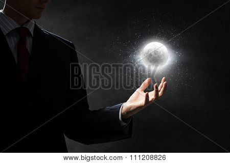 Close up of businessman holding moon planet in palm