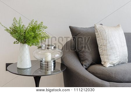 Plant In White Vase On Round Table With Sofa And Pillows