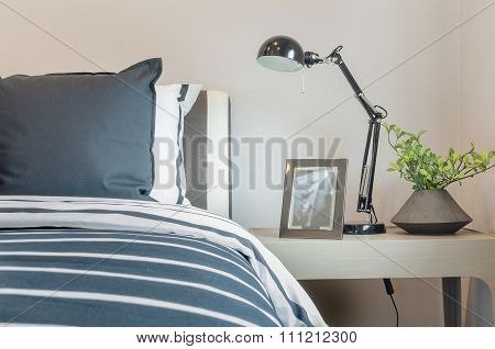 Black And White Pillows And Blanket On Bed With Black Lamp On Table Side
