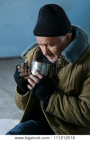 Homeless man holding his iron cup.