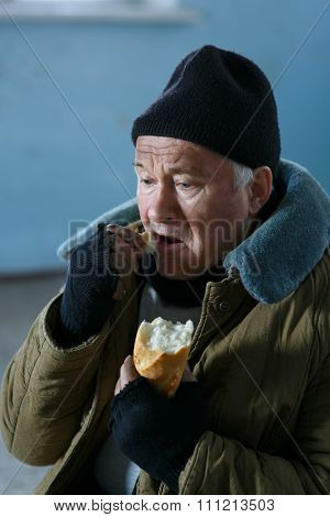 Depressed senior-aged beggar eating bread.