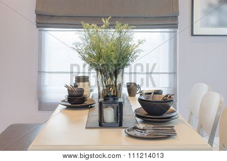 wooden dinning table with glass vase of plant