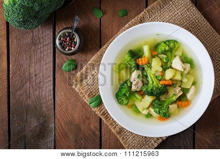 Chicken Soup With Broccoli, Green Peas, Carrots And Celery In A White Bowl On A Wooden Background In