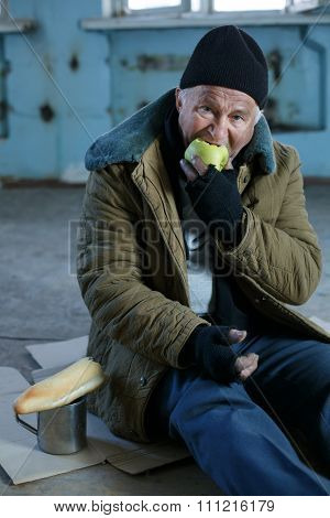 Senior homeless man eating an apple.