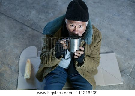 Homeless old man drinking from iron mug.