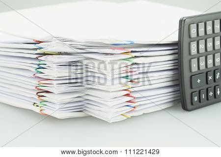 Pile Of Overload White Paperwork With Black Calculator Placed Vertical