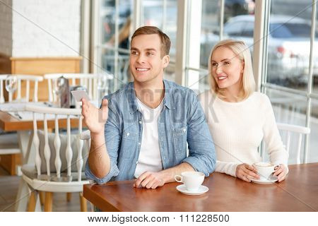 Delighted couple resting in the cafe