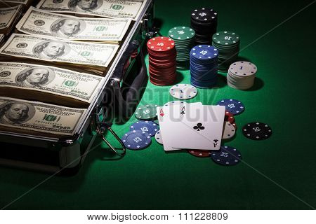 Money, cards and poker chips in the suitcase