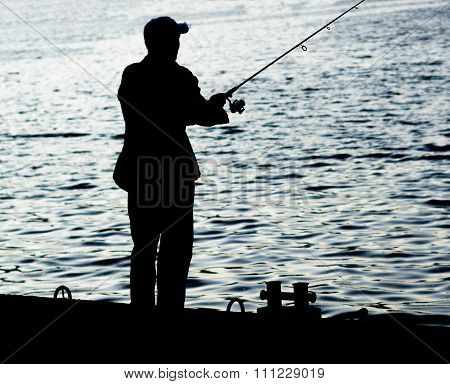 Fisherman Standing On Edge Of Dock With Fishing Rod Near River In City