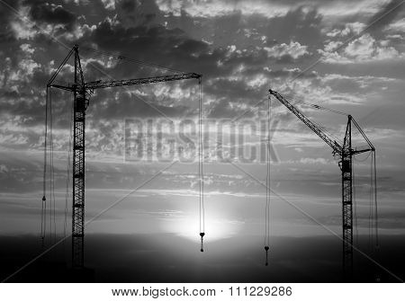 Hoisting Cranes Working On Beautiful Cloudy Sky With Sunset And Rays Of Light Background Black And W