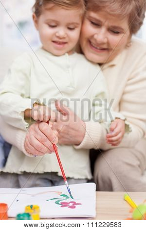 Pretty grandparent is teaching child to paint