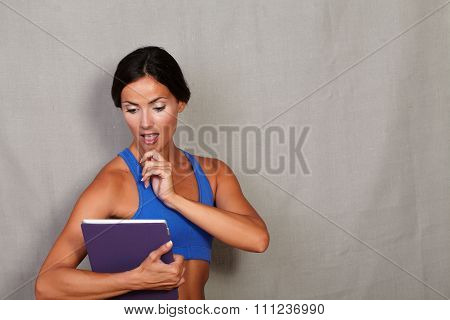 Surprised Woman While Looking At Tablet