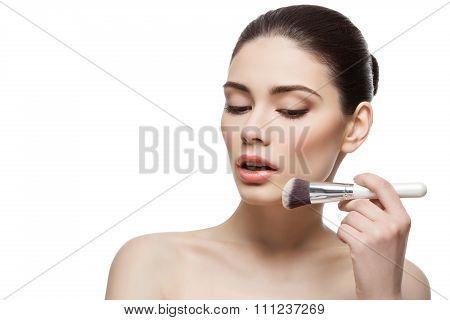 Beautiful girl applying powder with brush