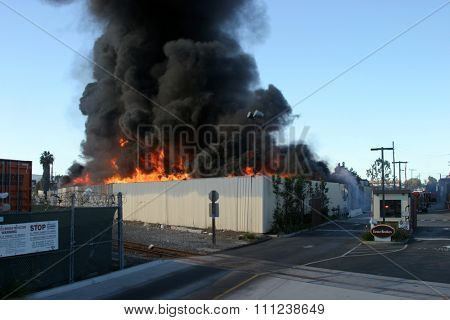 HARBOR GATEWAY, CALIFORNIA- DECEMBER 12, 2015: Fire erupts at recycling yard in Harbor Gateway. Flames and Acrid Black Smoke fill the air during a fire in Harbor Gateway, California Dec. 12, 2015
