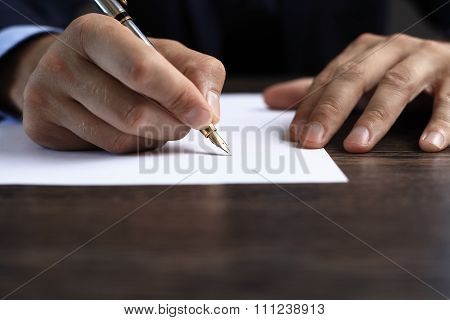 Man signing a document or writing correspondence with a close up view of his hand with the pen and s