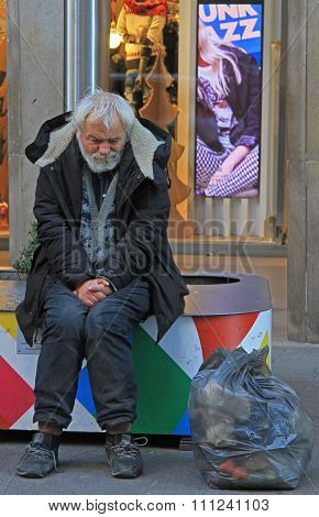 homeless is trying to warm up on the street in Milan, Italy