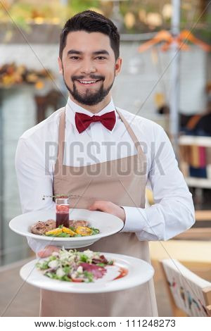Handsome young waiter is working in restaurant
