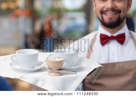 Handsome male cafe worker is serving a client