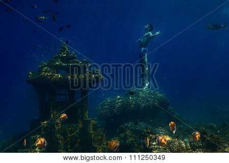 Underwater shot of the man moving on depth over coral reef