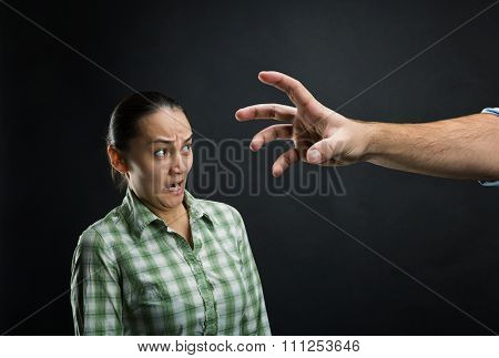 Young woman frightened with huge human hand over black