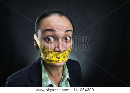 Businesswoman with tape ruler round her face over grey