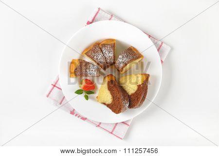 sliced marble bundt cake on white plate and checkered dishtowel