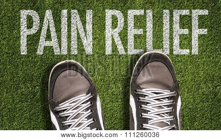 Top View of Sneakers on the grass with the text: Pain Relief