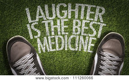 Top View of Sneakers on the grass with the text: Laughter Is The Best Medicine