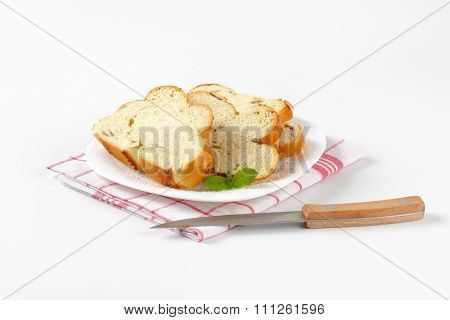 slices of sweet braided bread on white plate and checkered dishtowel