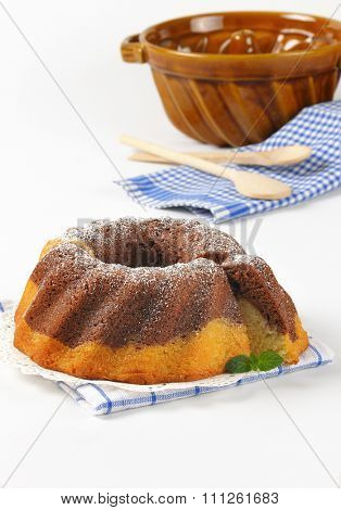 marble bundt cake, bundt cake pan, wooden spoons and checkered dishtowel on white background