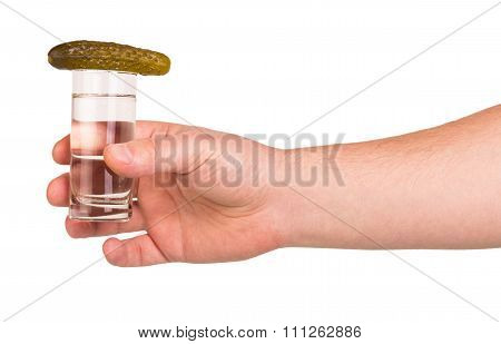 Hand with a glass of vodka and pickle