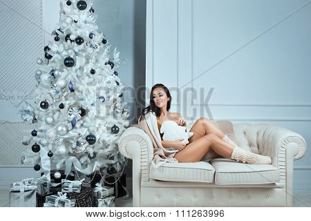 Girl In Warm Knitted Socks Sitting At Home  Couch.