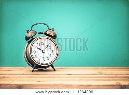 Retro And Vintage Style Of Old Fashioned The Alarm Clock On Wooden Table With Retro Blue Concrete Ba