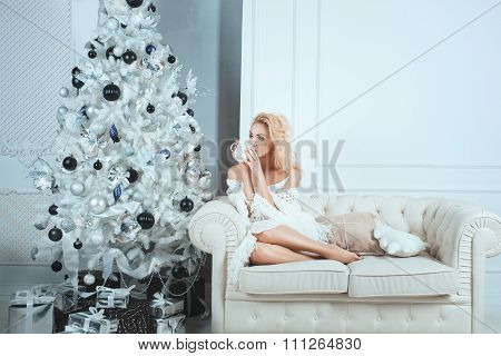 Girl Drinks From  Mug Near A Christmas Tree.