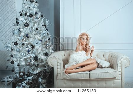 Cheerful Girl Sitting On A Sofa In Home Comfort.