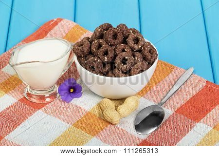 Chocolate corn-flakes and jug of milk