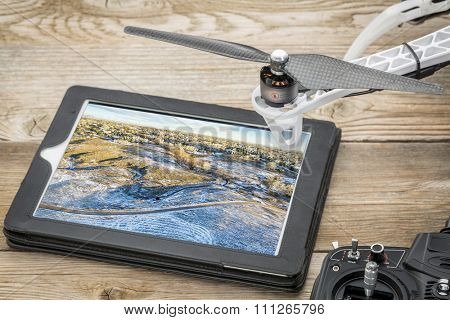 drone aerial photography concept - reviewing aerial picture of Colorado foothills near Fort Collins on a digital tablet with a drone rotor and radio control transmitter, winter scenery