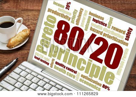 Pareto principle or eighty-twenty rule concept  word cloud on a laptop with a cup of coffee