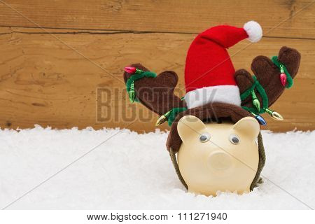 Christmas Savings,  Piggy Bank With Reindeer Antlers On Snow With Copy-space