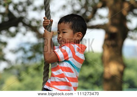 Japanese boy playing with Tarzan rope (3 years old)