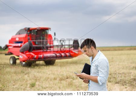 Businessman With Laptop And Cell Phone On Field