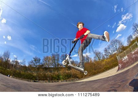 Boy Riding A Scooter Is Jumping At A Scooter Park