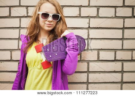 Blond Teenage Girl In Sunglasses With Skateboard